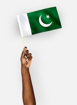 パキスタンのイスラム共和国の旗を振る人