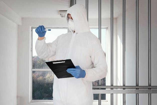 Человек в защитном костюме и взятие проб