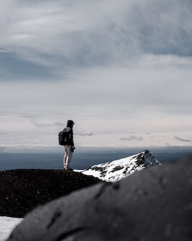 A person wearing backpack standing at the top of a mountain under cloudy sky