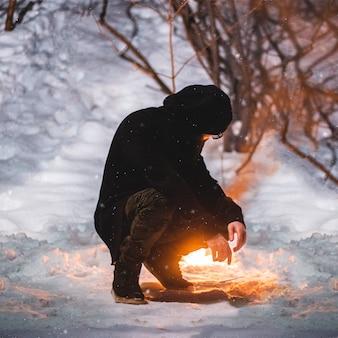 Человек в черном пиджаке, сидящий почти на снежном поле возле костра в дневное время