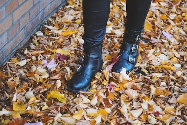 紅葉の中を歩く黒革のブーツを履いている人