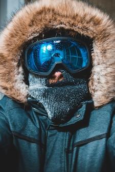 Человек, одетый в синее пальто и синие очки снега