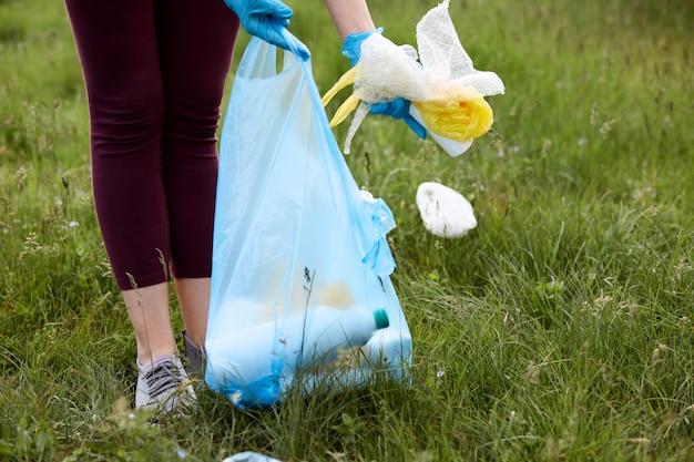Человек в бордовых штанах собирает мусор с зеленой травы и кладет мусор в пакет