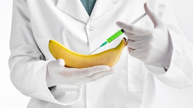 Person wearing gloves injecting a banana