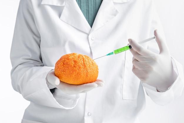 Persona che indossa guanti iniettando un'arancia