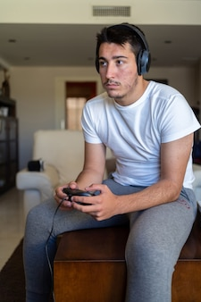 헤드폰을 착용하고 tv에서 비디오 게임을하는 사람