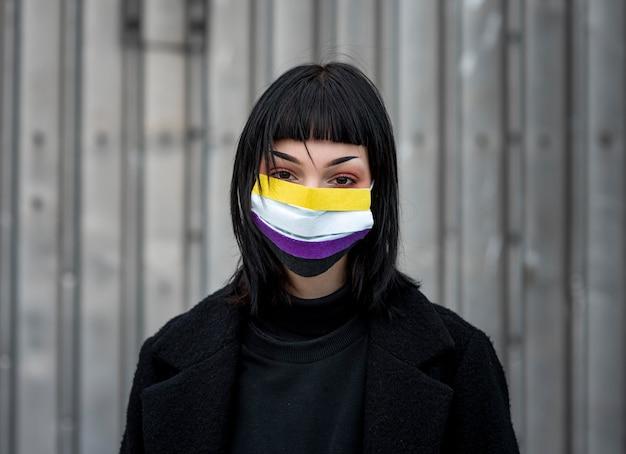 Persona che indossa una maschera medica non binaria
