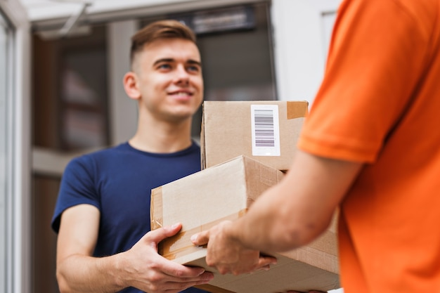 A person wearing an orange t-shirt is delivering parcels to a satisfied client. friendly worker, high quality delivery service.