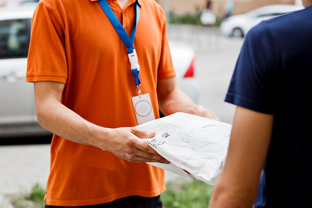 A person wearing an orange t-shirt and a name tag is delivering a parcel to a client. friendly worker, high quality delivery service.