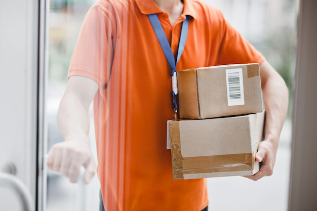 A person wearing an orange t-shirt and a name tag is standing behind the glass door and holding a door handle and parcels for the client. friendly worker, high quality delivery service.
