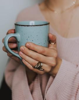 Persona che indossa un maglione rosa che tiene una tazza blu