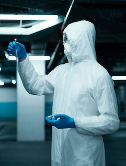 Persona che indossa una tuta di prevenzione durante il prelievo di campioni