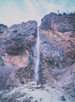 滝の近くに立っている赤いジャケットを着ている人