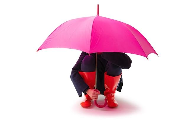 Человек, носящий красные резиновые туфли и зонтик от дождя, изолированные на белом фоне.