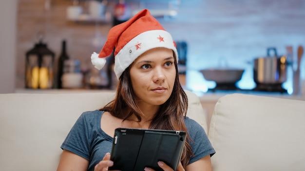サンタの帽子をかぶってデジタルタブレットで作業している人