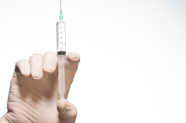Person wearing a surgical glove holding a syringe isolated on a white background