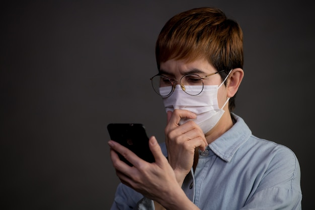Person wearing surgical mask and using their phone looking worried and concerned about the pandemic outbreak and news from social media