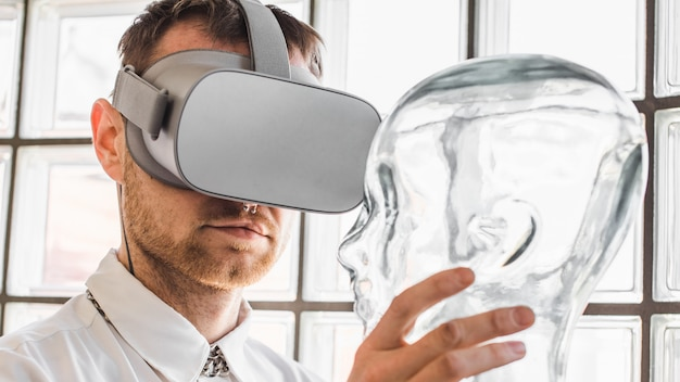 Person wearing virtual reality goggles holding a transparent mannequin