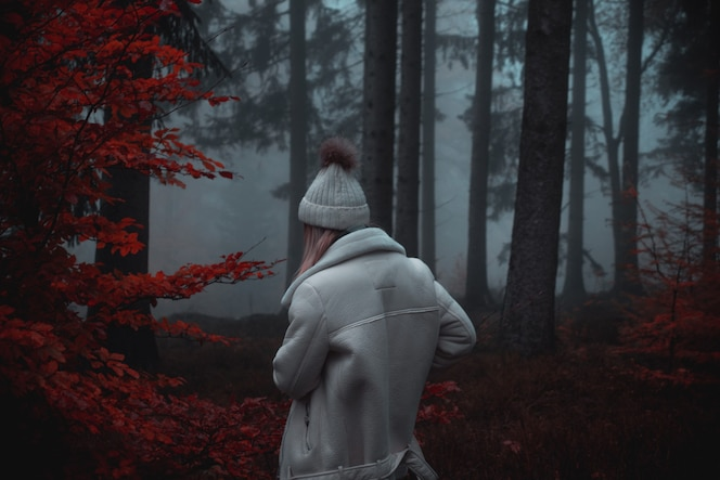 Person wearing white coat and white hat in forest