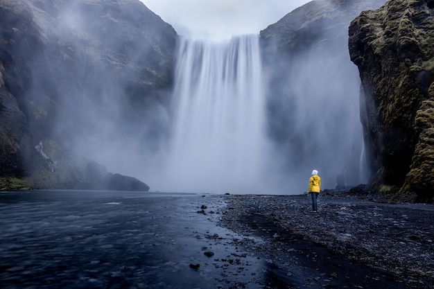 Person wearing a yellow jacket standing at the mesmerizing waterfall