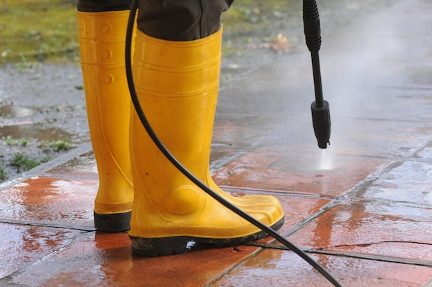 Person wearing yellow rubber boots with high-pressure water nozzle cleaning the dirt in the tiles