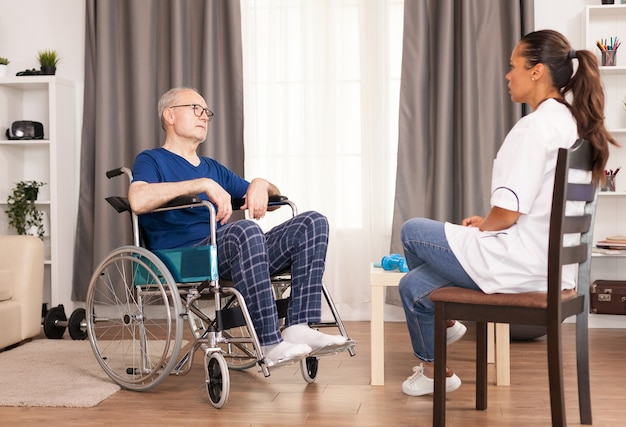 Person in whellchair talking with nurse in the doctor's office. disabled disability old person with medical worker in nursing care home assistance, healthcare and medicine service