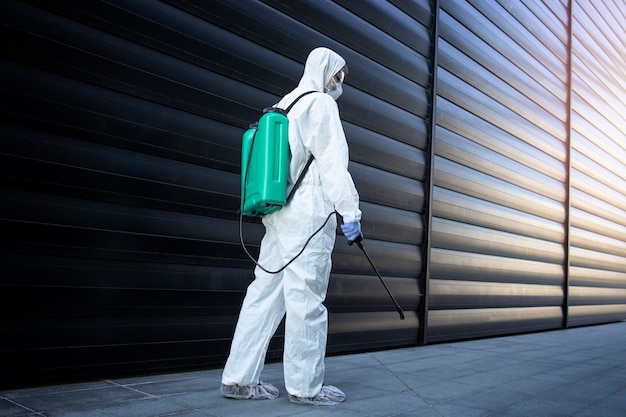 Person in white chemical protection suit doing disinfection and pest control with sprayer to kill insects and rodents