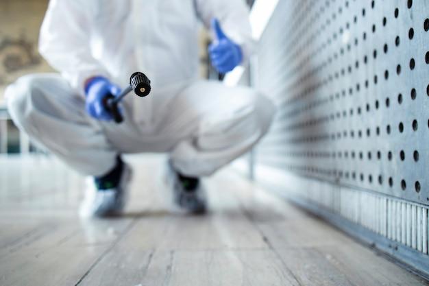 Persona in tuta di protezione chimica bianca che esegue la disinfezione delle aree pubbliche per fermare la diffusione del virus corona altamente contagioso