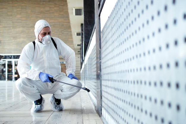 Person in white chemical protection suit doing disinfection of public areas to stop spreading highly contagious corona virus