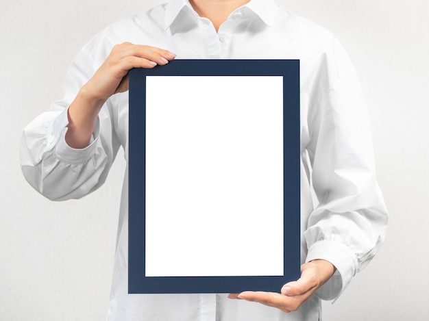 Person in white coat holds empty mockup frame