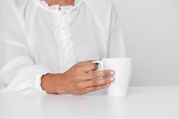 Person in white shirt holding a cup