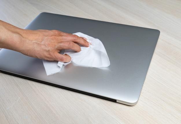 コロナウイルスcovid-19のためにラップトップをアルコールワイプで拭く人