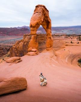美しいグランドキャニオンの岩の前に毛布が立っている人