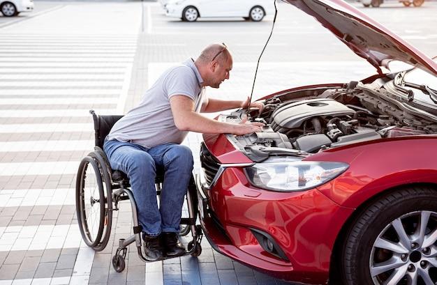 Человек с ограниченными физическими возможностями проверить двигатель своего автомобиля на стоянке