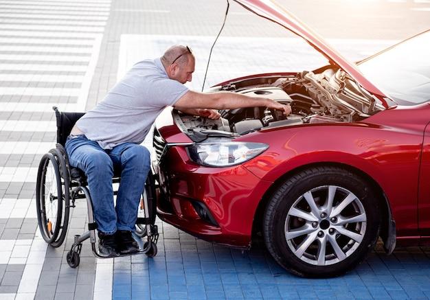 身体障害者が駐車場で車をチェックエンジン