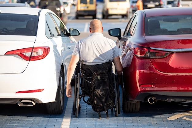 赤い車の車いすに乗る身体障害者