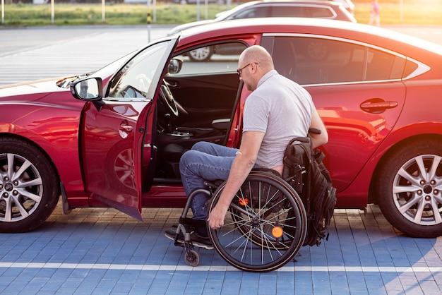 Человек с ограниченными физическими возможностями, садясь в красный автомобиль с инвалидной коляски