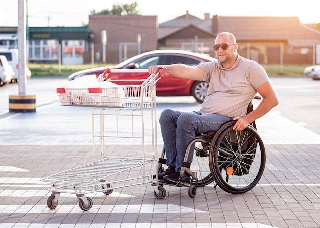 スーパーマーケットの駐車場で自分の前にカートを押す身体障害者