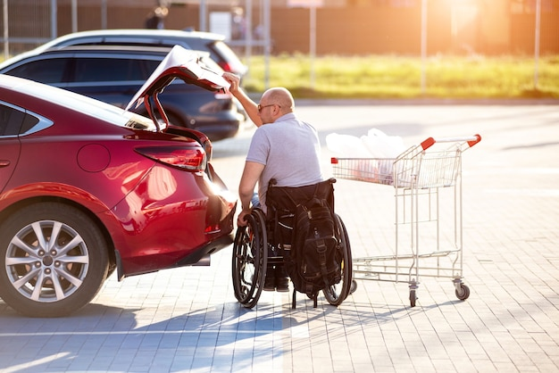 身体に障害のある人がスーパーマーケットの駐車場で車のトランクに買い物をする
