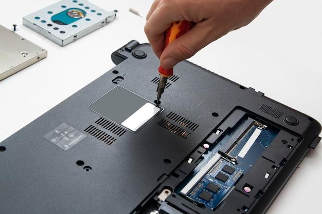 ドライバーを持つ人は、部品を交換して修理するために部品のラップトップケースを分解します