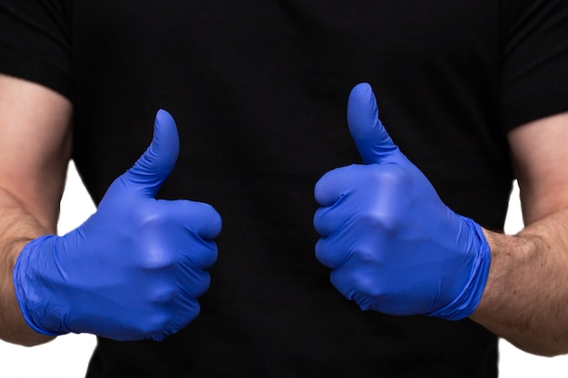 Person with blue latex gloves for protection coronavirus with thumbs up, covid-19 self isolation or quarantine at home support doctors and nurses