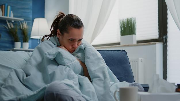Человек с болезнью чувствует холод с одеялом и подушкой на диване