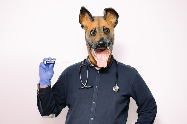 Person with dog mask showing a thermometer