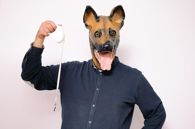 Человек в маске собаки показывает прогулочный поводок