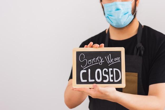 Человек с маской на лице держит табличку с надписью «извините, мы закрыты» на белой стене
