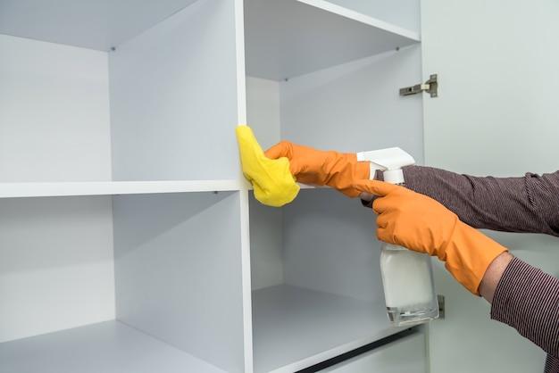 장갑과 청소 세트를 가진 사람은 주방 가구를 세척합니다. 자신을 보호하다. 집안일