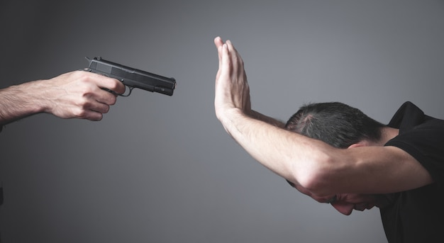 Person with a handgun with a his victim.