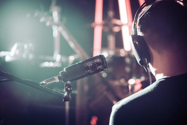 Человек с наушниками и студийным микрофоном крупным планом, в студии звукозаписи или концертном зале, с ударной установкой.