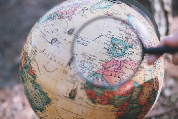 Person with magnifying glass looking at globe