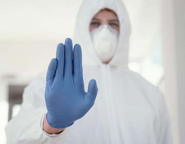 Persona con mascherina medica che indossa un equipaggiamento protettivo contro un rischio biologico